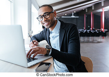 Handsome businessman smiling working on his laptop -...