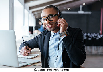 Stylish smart businessman using headphones during his work...