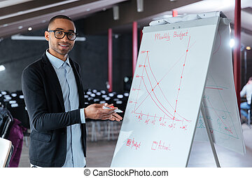Businessman presenting something on flip chart - Smart...