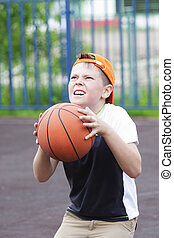 Boy going to throw ball into basket closeup photo at outdoor...