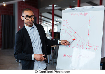 Businessman pointing on the flipchart - Businessman pointing...