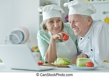 Senior couple at kitchen  cooking with laptop