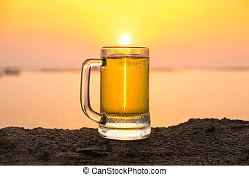 Glass of light beer at the beach with the sun , summer and...