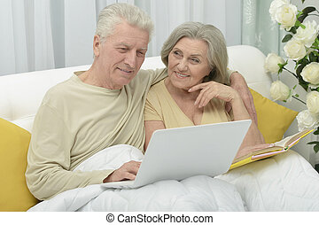 Senior couple in bed - Senior couple resting and reading in...