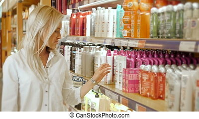 Portrait of Young Beautiful Blonde Woman Reading Label of Shampoo In Supermarket