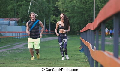 Man and woman commit a jog. They are young and attractive, communicate with each other positively.