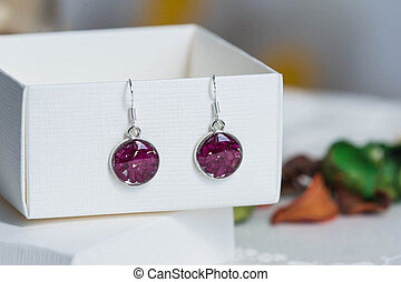Earrings made of epoxy resin and natural rose petals close...