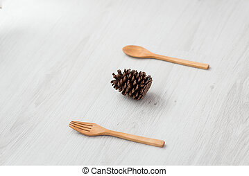pine cone with fork and spoon on grey wooden table.