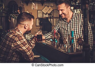 Handsome bartender pouring a pint of beer to customer in a...