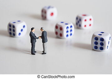 Businessmen hand shaking with dice. Business risk concept.