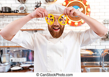 Funny chef cook looking through slices of yellow bell pepper...