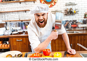 Angry bearded chef cook holding meat cleaver knife and...