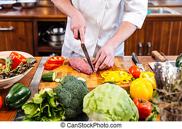 Professional chef cook cutting uncooked meat and fresh...