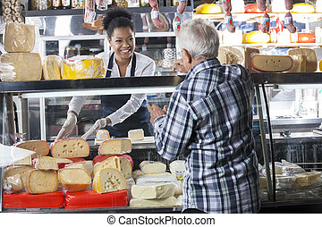 Saleswoman Selling Cheese To Senior Man At Shop - Happy...
