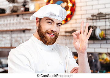Cheerful chef cook showing ok sign on the kitchen - Portrait...