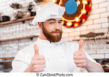 Smiling attractive chef cook showing thumbs up on the...