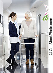 Senior Woman Looking At Physiotherapist While Using Walker