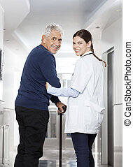 Rear View Of Happy Doctor Walking With Senior Patient - Rear...