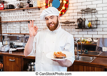 Chef holding salmon steak on plate and showing ok gesture -...