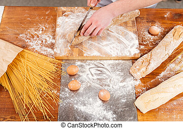 Wooden table of baker cutting fresh bread on the kitchen -...