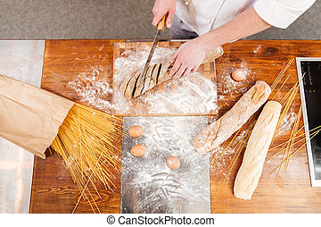 Top view of man baker cutting bread on kitchen - Top view of...