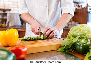 Hands of chef cook cutting vegetables and making salad -...
