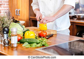 Chef cook cutting yellow bell pepper on the kitchen -...