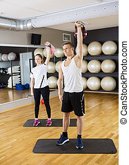 Fit Friends Lifting Kettlebells In Gym