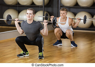 Friends Lifting Barbell While Crouching In Gym - Young male...