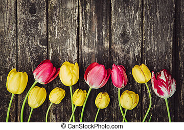 Yellow and pink tulips on grey wooden shabby table