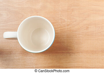 White cup top view on wooden table