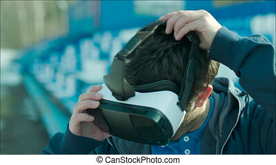 Guy putting on VR glasses and looking around - Young man...