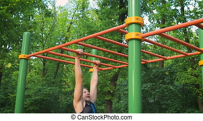 Muscular man doing pull-ups on horizontal bar go to the...