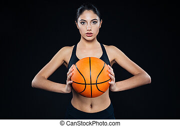 Pretty fitness woman holding and posing with basketball ball...