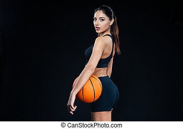 Fitness woman holding basketball ball and looking back at...