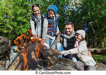 happy family roasting marshmallow over campfire - camping,...