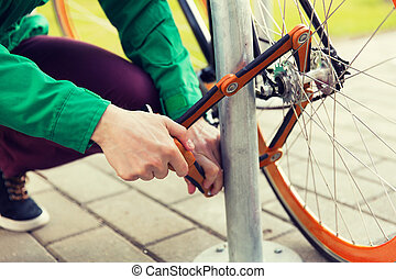 close up of man fastening bicycle lock on parking - people,...