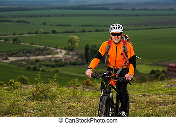 Young man cycling on a rural road through green meadow -...
