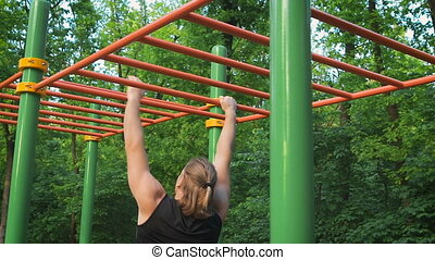 Muscular man doing pull-ups on horizontal bar. go to the...