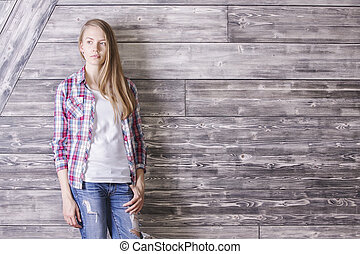 Female against wooden wall - Thoughtful casually dressed...