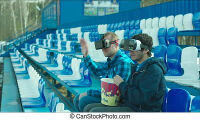 Upset guys in VR glasses sitting at the stadium -...