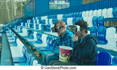 Friends in VR glasses rooting active on the stadium tribune...