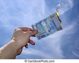 hand taking twenty burning euro on a blue sky background