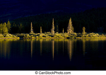 Dawn on Swiftcurrent Lake - A single shaft of dawn light...