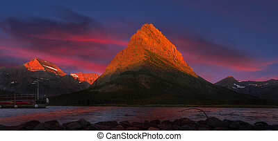 Swiftcurrent Lake at Dawn - Colorful sunrise over...