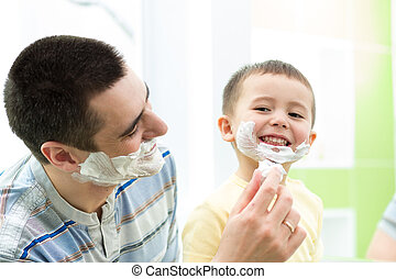 playful father and his son having fun in bathroom - shaving...