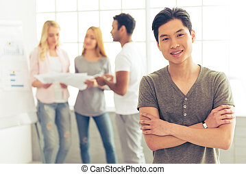 Young people working - Handsome Asian guy is looking at...