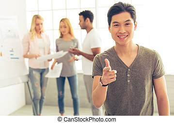 Young people working - Handsome Asian guy is smiling,...