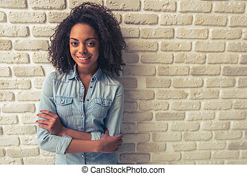 Beautiful Afro American girl is looking at camera and...