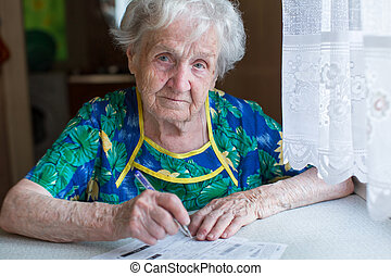 Woman fills in receipts for utiliti - Elderly woman fills in...